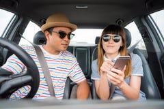 Opinião dianteira o homem asiático e a mulher dos pares engraçados do momento que sentam-se no carro Apreciando o conceito do cur imagens de stock