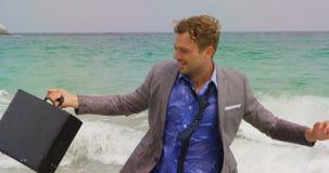 Opinião dianteira o homem de negócios caucasiano que corre com a pasta no mar na praia 4k filme