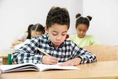 Opinião dianteira o rapaz pequeno em processo de fazer o teste na escola imagem de stock
