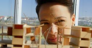 Opinião dianteira os arquitetos fêmeas caucasianos que olham o modelo de construção no escritório 4k vídeos de arquivo