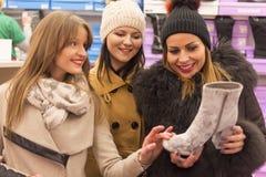 Opinião dianteira três jovens mulheres em uma sapataria foto de stock royalty free