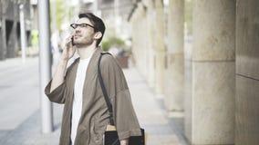 Opinião dianteira um homem de negócios considerável pensativo que fala seu telefone esperto na rua e que olha acima Foto de Stock Royalty Free