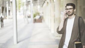 Opinião dianteira um homem de negócios considerável que fala seu telefone esperto na rua e que olha a câmera Foto de Stock