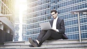 Opinião dianteira um homem de negócios novo considerável que trabalha com um portátil dentro na cidade Imagem de Stock Royalty Free
