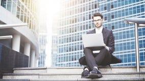 Opinião dianteira um homem de negócios novo considerável que trabalha com um portátil dentro na cidade Escadas Imagem de Stock