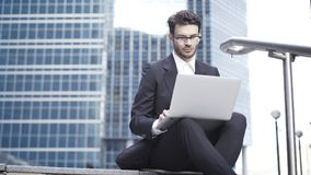 Opinião dianteira um homem de negócios novo considerável que trabalha com um portátil fora Foto de Stock Royalty Free