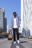 Opinião dianteira um homem novo do africano negro que anda na rua que veste o revestimento elegante e que guarda um saco ao usar  foto de stock royalty free
