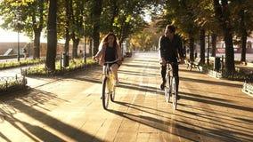 Opinião dianteira um par novo ou os amigos que montam suas bicicletas no parque ou no bulevar da cidade no verão Povos, lazer filme