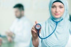 Opinião dianteira uma mulher árabe do doutor que mostra o estetoscópio imagem de stock royalty free