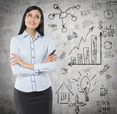 Opinião dianteira uma mulher pensativa com mãos cruzadas Um conceito de um clique Os ícones do negócio são tirados na parede Fotografia de Stock