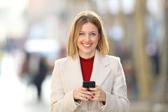 Opinião dianteira uma mulher que guarda um telefone que olha o imagens de stock royalty free