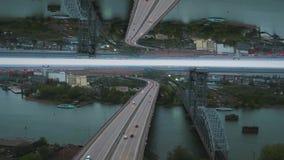 Opinião do amanhecer da cidade com ponte do rio, construção inacabado e muitas árvores verdes, efeito do horizonte do espelho med vídeos de arquivo