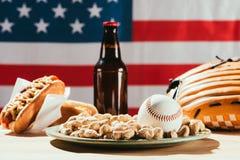 opinião do close-up da bola do basebol na placa com amendoins e garrafa de cerveja com quente Fotografia de Stock Royalty Free