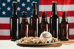 opinião do close-up da bola do basebol na placa com amendoins e garrafas de cerveja com americano Fotografia de Stock Royalty Free