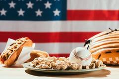 opinião do close-up da bola do basebol na placa com amendoins, a luva de couro e os cachorros quentes na tabela connosco Imagens de Stock Royalty Free
