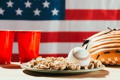 opinião do close-up da bola do basebol na placa com amendoins, os copos plásticos vermelhos e a luva de beisebol na tabela connos Fotografia de Stock Royalty Free