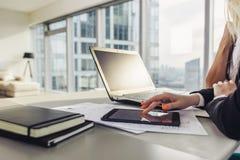 Opinião do close-up da mesa de escritório: portátil, cadernos, papéis, tablet pc na sótão de luxo moderna fotos de stock royalty free