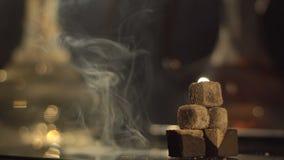 A opinião do close-up da pirâmide de três brasas no backgroud borrado da mudança colore o cachimbo de água A composição é filme