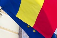 Opinião do close-up das bandeiras de ondulação de Romênia e da União Europeia A bandeira da UE é escondida com bandeira romena foto de stock