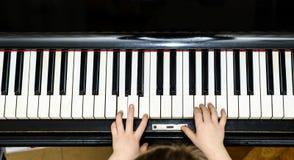 Opinião do close-up das mãos da menina e do teclado de piano fotografia de stock