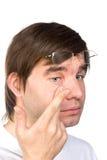 Opinião do close up do olho marrom de um homem ao introduzir um c corretivo Imagens de Stock