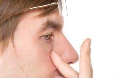 Opinião do close up do olho marrom de um homem ao introduzir um c corretivo Imagem de Stock