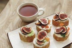 opinião do close-up dos canapes com figos e do copo do chá Fotos de Stock Royalty Free