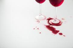 Opinião do close-up dos copos de vinho com o vinho tinto e o vinho derramados Fotografia de Stock