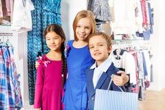 Opinião do close-up duas meninas e um menino na loja Fotos de Stock Royalty Free
