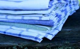 Opinião do close up em toalhas de cozinha do grupo no fundo de madeira na natureza Fundo borrado fotos de stock royalty free