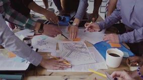 Opinião do close-up a equipe nova do negócio que trabalha junto perto da tabela, conceituando vídeos de arquivo