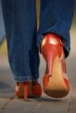 Opinião do Close-up a fêmea no passeio vermelho das sapatas Foto de Stock Royalty Free