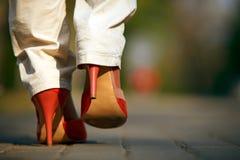 Opinião do Close-up a fêmea no passeio vermelho das sapatas Foto de Stock
