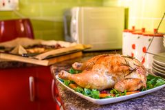 Opinião do close up a galinha roasted na placa branca na mesa de cozinha imagens de stock
