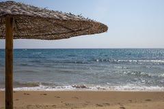 Opinião do close up do guarda-chuva tecido do telhado cobrido com sapê que está apenas no beira-mar Pegadas na areia fina e no cr fotos de stock royalty free