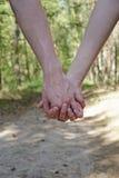 Opinião do close-up homens novos e mulher que guardam as mãos na floresta Imagem de Stock Royalty Free