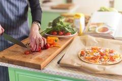 A opinião do close-up a jovem mulher s entrega vegetais do corte a bordo para a pizza de acordo com o livro da receita foto de stock