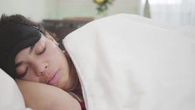 Opinião do close-up a mulher afro-americano atrativa que encontra-se sob a cobertura branca com máscara preta do sono Descanso bo video estoque