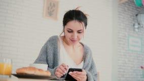 Opinião do close-up a mulher que tem o café da manhã e o Internet da consultação, usando o écran sensível A menina leu novo no sm Fotografia de Stock Royalty Free