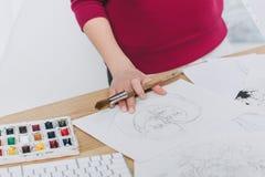 Opinião do close-up a mulher que trabalha em ilustrações na tabela de funcionamento foto de stock royalty free