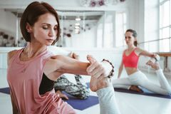 Opinião do close-up na ioga praticando da mulher saudável forte exerciese na esteira da aptidão na classe branca do esporte imagem de stock royalty free