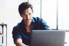 Opinião do close up o desenhista novo que usa o laptop no estúdio coworking moderno Janelas panorâmicos no fundo borrado Fotografia de Stock