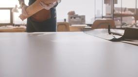 Opinião do close-up o homem de negócios profissional do artesão que espalha uma parte de couro grande na tabela de fabricação cla video estoque
