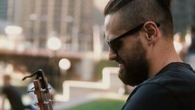 Opinião do close-up o homem novo no restrung dos óculos de sol, corda em mudança na guitarra na rua no dia de verão ensolarado vídeos de arquivo