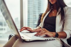 Opinião do close-up o journalista fêmea elegante que escreve um artigo usando o netbook que senta-se no escritório moderno fotografia de stock royalty free