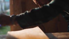Opinião do close-up os homens que trabalham com serra de vaivém elétrica e a prancha de madeira r video estoque