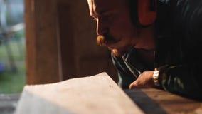 Opinião do close-up os homens que trabalham com serra de vaivém elétrica e a prancha de madeira r vídeos de arquivo
