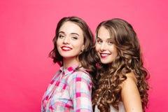 Opinião do estúdio meninas bonitas com cabelo ondulado magnífico e os bordos vermelhos, em um estilo do moderno com um feliz, bon foto de stock