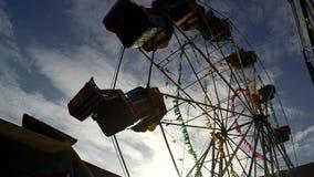 Opinião do lado de baixo de uma roda de Ferris barata sob o céu azul filme