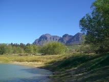 Opinião do lago com árvores e montanhas fotos de stock royalty free